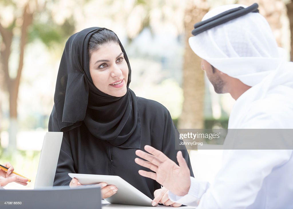 Emirati businesswoman in discussion with arab business colleague