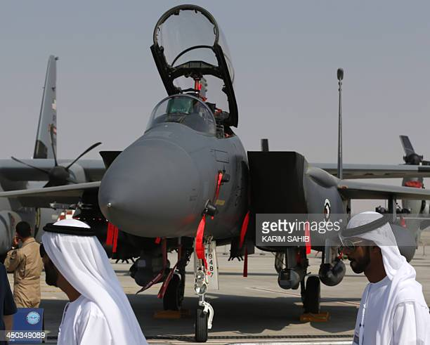 Emirati citizens walk past US made F15 Eagle fighter jet displayed at the Dubai Airshow on November 18 2013 The biennial Dubai Airshow got off to a...