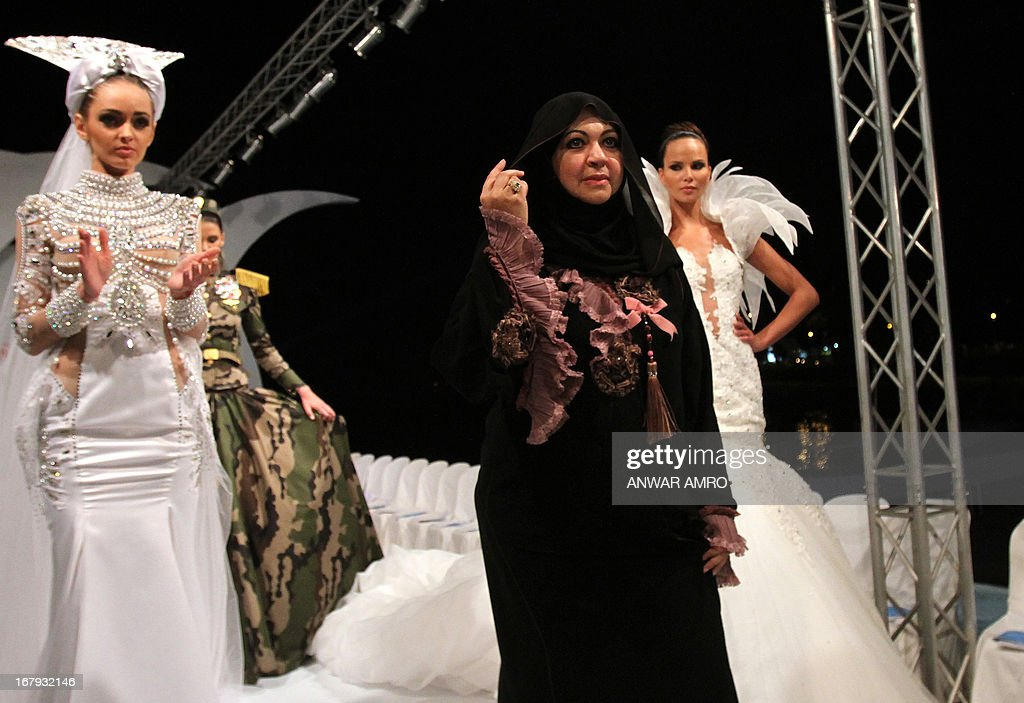 Emirati designer Mona al-Mansouri (C) stand amidst models presenting her creations during a fashion show in Beirut on May 2, 2013.