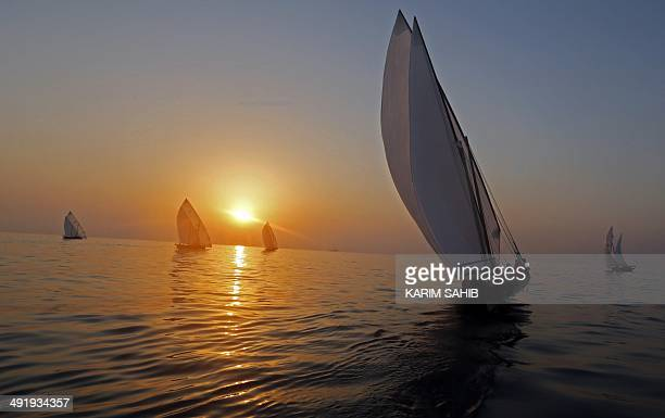 Emirati dhows sail towards the finishing line in the the AlGaffal traditional longdistance dhow sailing race between the island of Sir Bu Nair near...