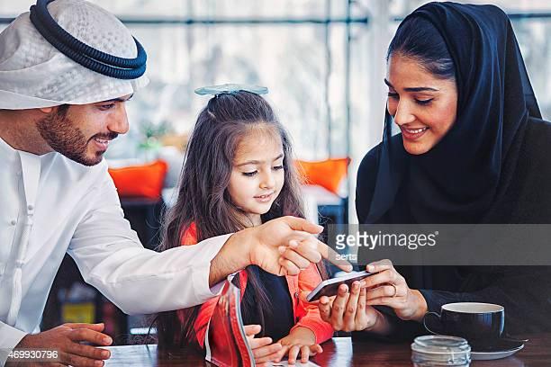 Emirati family enjoying with smartphone at cafe