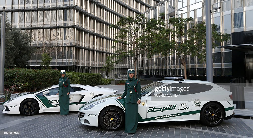 Emirati female police officers pose in front of Ferrari (R) and Lamborghini (L) police vehicles at the foot of the Burj Khalifa tower in the Gulf emirate of Dubai on April 25, 2013. Dubai police showed off a new Ferrari they will use to patrol the city state, hot on the heels of a Lamborghini which joined the fleet earlier.