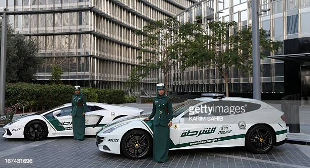Emirati female police officers pose in front of Ferrari and Lamborghini police vehicles at the foot of the Burj Khalifa tower in the Gulf emirate of...