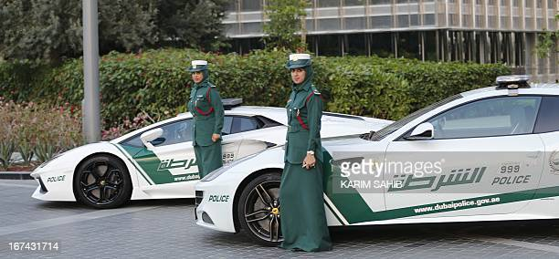 Emirati female police officers pose in front of Lamborghini and Ferrari police vehicles on April 25 2013 in the Gulf emirate of Dubai Dubai police...