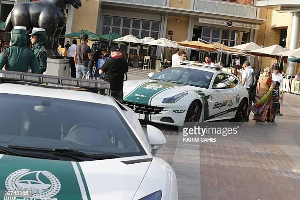 Emirati female police officers stand next to Lamborghini and Ferrari police vehicles in the Gulf emirate of Dubai on April 25 2013 Dubai police...