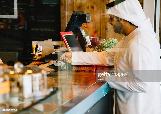 Emirati man paying via credit card at cafe