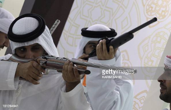 Emirati men check hunting rifles on September 5 on the first day of the Abu Dhabi International Hunting and Equestrian exhibition which offers...