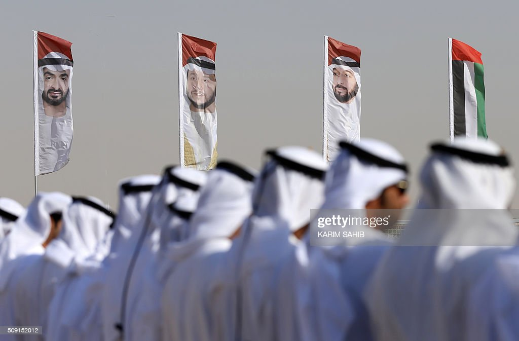 Emirati men perform a traditional dance in front of flags bearing portraits of Abu Dhabi's Crown Prince Sheikh Mohammed bin Zayed al-Nahyan (L), Sheikh Sultan Bin Zayed al-Nahyan (C), UAE President Sheikh Khalifa bin Zayed Al-Nahyan (R) during the Sheikh Sultan Bin Zayed al-Nahyan heritage festival, held at the Sweihan racecourse in Al-Ain on February 9, 2016. / AFP / KARIM SAHIB