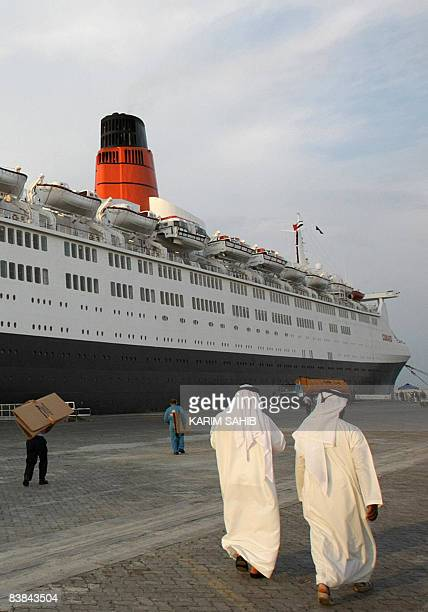 Emirati men walk past the Queen Elizabeth 2 cruise liner as it rests in port in Dubai on November 27 2008 The UAE flag was raised today during a...