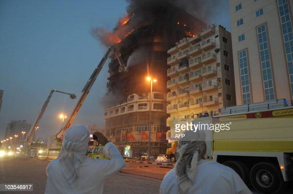 Emirati men watch the flames and smoke ascending from an apartment block in Sharjah city in the UAE on July 6 following a gas pipe explosion...