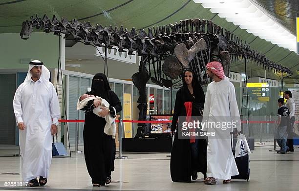 Emirati passangers walk past the 140millionyearold dinosaur put on display at Abu Dhabi international airport until October on August 11 2008 The...
