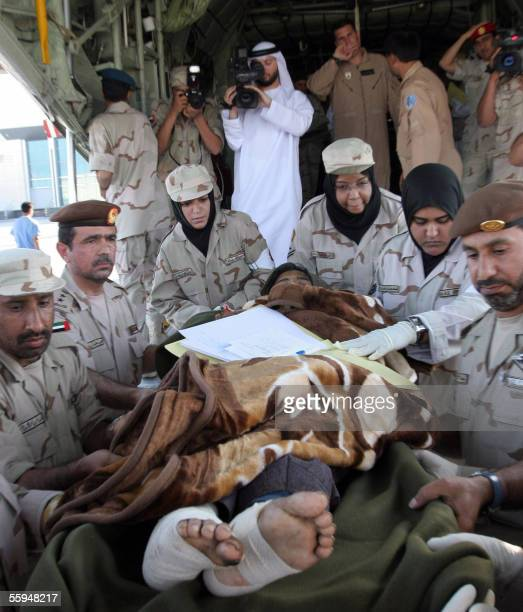 Emirati soldiers carry a Pakistani earthquake survivor out of a military plane at Abu Dhabi's military airport 18 October 2005 Ten Pakistani injured...