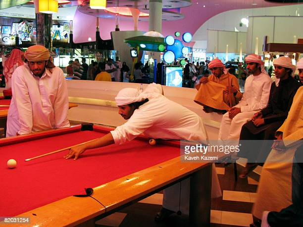 Emirati teenage male youth in their traditional white dress gather around and play on a pool table on Friday night in the Mall of Emirates games hall...