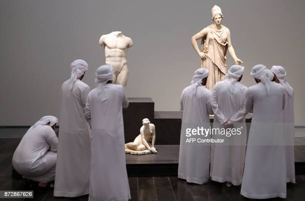 TOPSHOT Emirati visitors look at exhibits during the opening of the Louvre Abu Dhabi Museum on November 11 2017 on Saadiyat island in the Emirati...