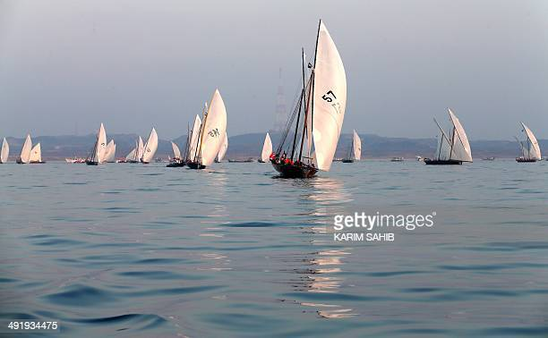 Emiratis sail during the AlGaffal traditional longdistance dhow race towards the finish line after racing between the island of Sir Bu Nair near the...
