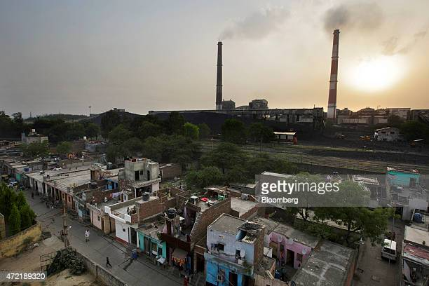 Emissions billow from smokestacks at the NTPC Ltd Badarpur coalfired power plant near residential property as the sun sets in Badarpur Delhi India on...