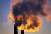 Harmful emissions from the plant pipe against the background of the setting sun