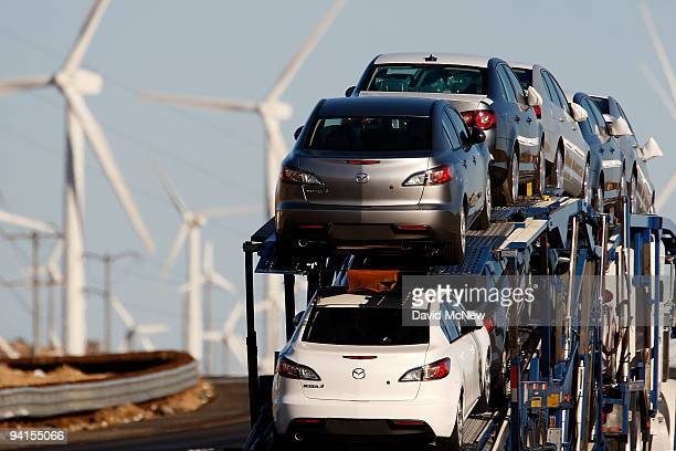 Emissionsproducing diesel trucks and cars pass nonpolluting windmills along the 10 freeway on December 8 2009 near Banning California Sustained...