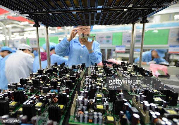 Emloyees work on the production line of motherboard and chip of network switch at FiberHome Technologies Group on July 27 2015 in Wuhan China...