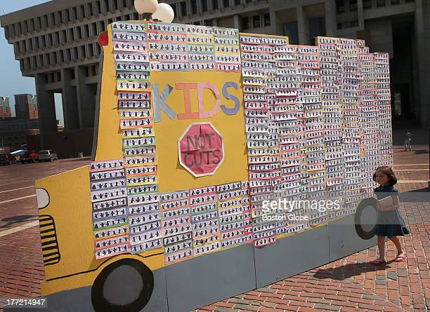 Emma AugerPerry from Everett walks past a mockup of a school bus at Boston City Hall Plaza The bus was set up for a news conference for Massachusetts...