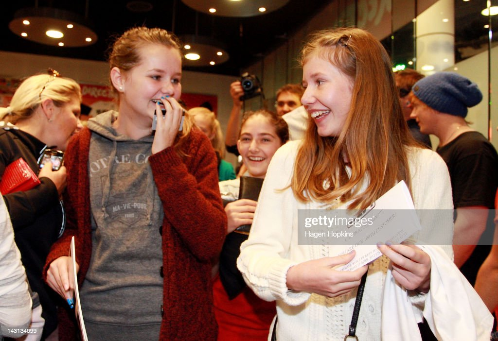 Emma Burke (R), 14, celebrates with twin sister Lucy after winning double pass to One Direction's Wellington concert by becoming the 100th customer at the official One Direction merchandise store on April 20, 2012 in Wellington, New Zealand. The 1D fan store will sell official merchandise for four days only, closing on Monday, April 20. One Direction is on tour in New Zealand performing a show in Auckland and Wellington before returning to the UK.