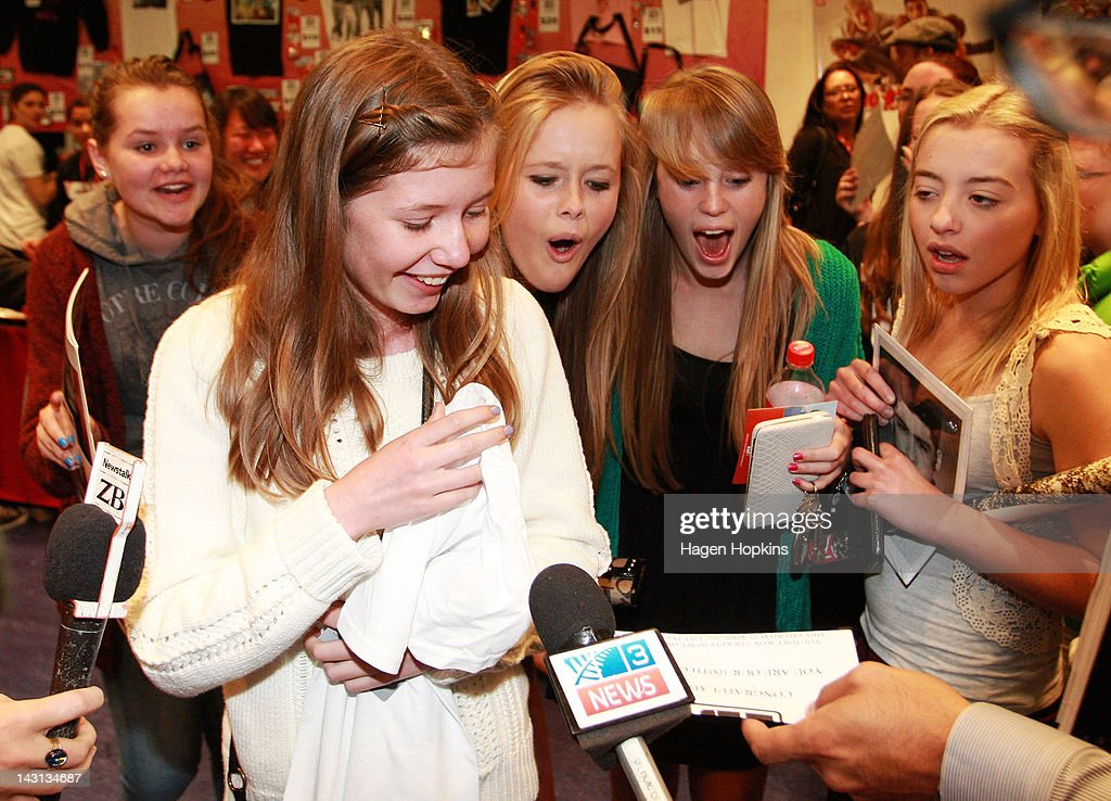 Emma Burke (L), 14, is handed a double pass to One Direction's Wellington concert after becoming the 100th customer inside the official One Direction merchandise store on April 20, 2012 in Wellington, New Zealand. The 1D fan store will sell official merchandise for four days only, closing on Monday, April 20. One Direction is on tour in New Zealand performing a show in Auckland and Wellington before returning to the UK.
