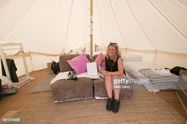 Emma Catchpole enjoys a drink of champagne inside her bell tent at the PopUp Hotel which offers festival goers alternative luxury camping close to...