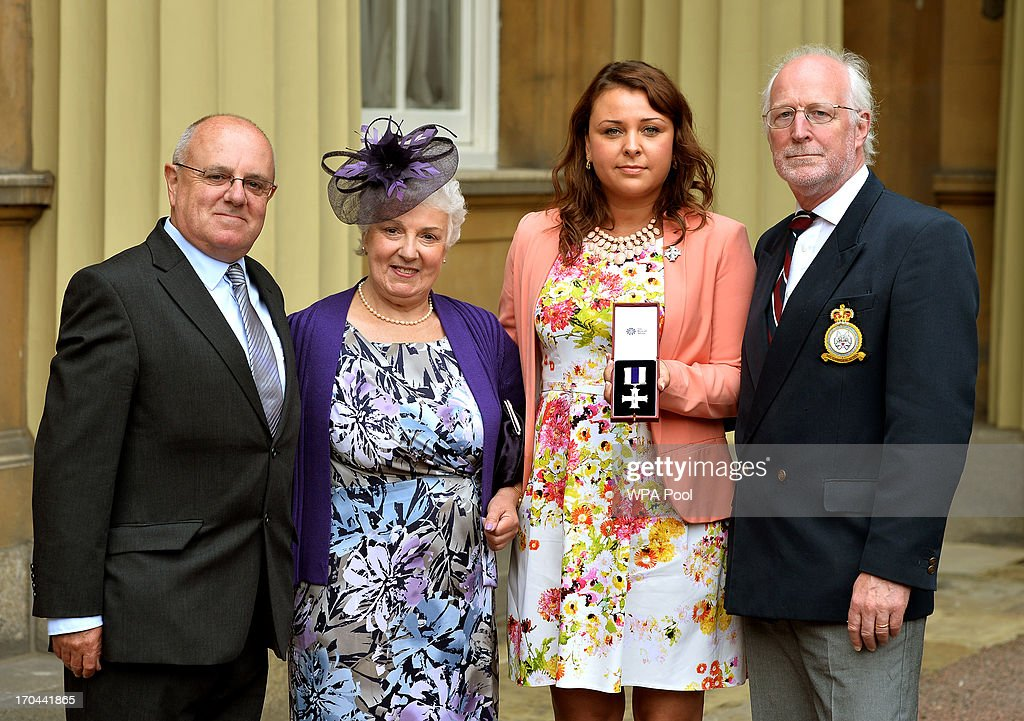 Emma Guy holds the Military Cross awarded posthumously to her husband Alex, with (L - R), his uncle Alec Wilson, mum Aileen and father Andrew after it was presented to her by Queen Elizabeth II, at the Investiture ceremony at Buckingham Palace on June 13, 2013 in London, England.