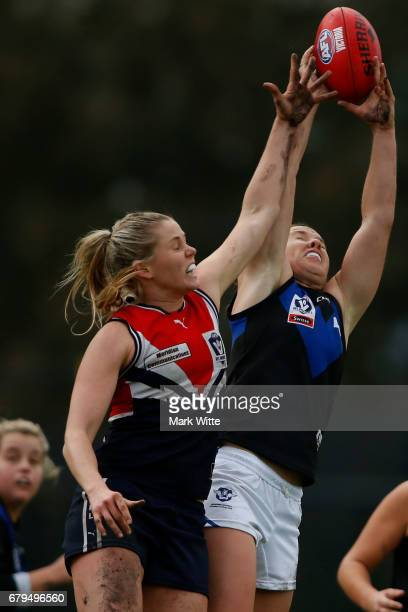 Emma Kearney of Melbourne Uni takes a mark infront of Katie Brennan of Darebin Falcons during the round one VFL Women's match between the Darebin...
