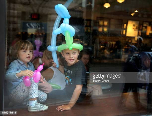 Emma Muller left holds her new pink balloon dog as her big brother Santino Muller right plays with his balloon sword while their parents enjoy a cup...