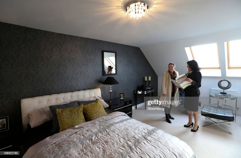 Emma Porter, a potential house buyer, left, is shown around the bedroom of a show home by Donna Beange, a sales advisor, at a Barratt Developments Plc construction site for residential housing in Bedford, U.K., on Thursday, Dec. 13, 2012. Barratt Developments Plc, the U.K.'s largest homebuilder by volume, said advance sales rose 21 percent as government initiatives to boost homebuilding lifted private reservations in the autumn selling season. Photographer: Chris Ratcliffe/Bloomberg via Getty Images