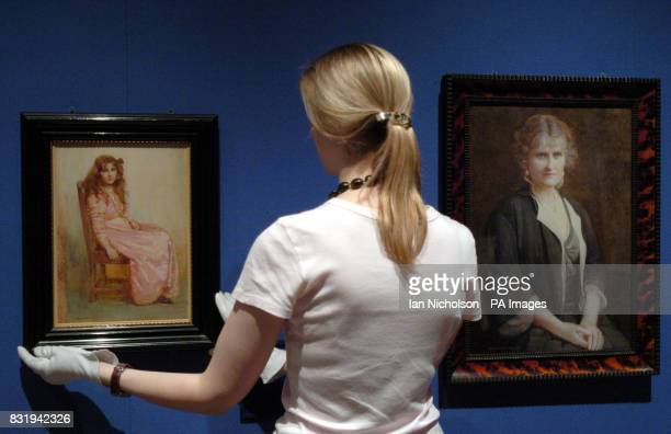Emma Shaw of the Royal Collection adjusts a portrait dated 1907 of the sevenyearold Lady Elizabeth BowesLyon by the artist Mabel Hankey who also...