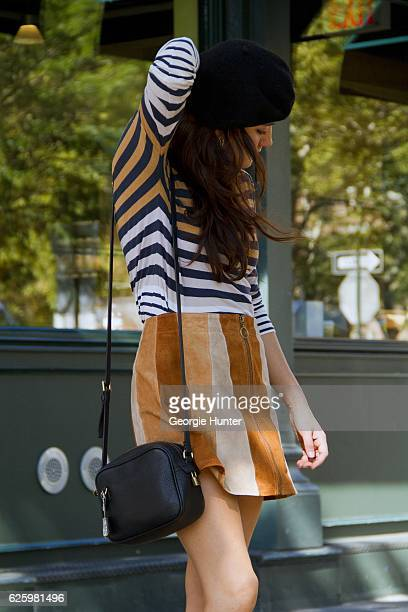 Emma Sousa wearing blue white and tan horizontal striped long sleeved cotton top by Old Navy tan brown and cream striped high waisted short suede...