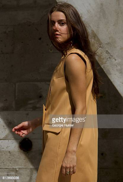 Emma Sousa wearing nude beige tailored Won Hundred double breasted sleeveless vest blazer jacket dress and silver HM rings and gold round drop...