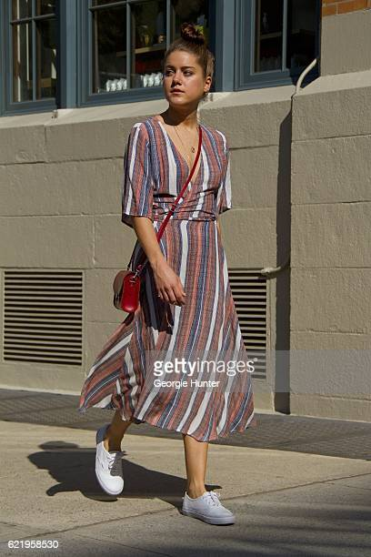 Emma Sousa wearing rayon red white and blue striped Just Female midi wrap dress with waist tie and three quarter length sleeves white leather low top...