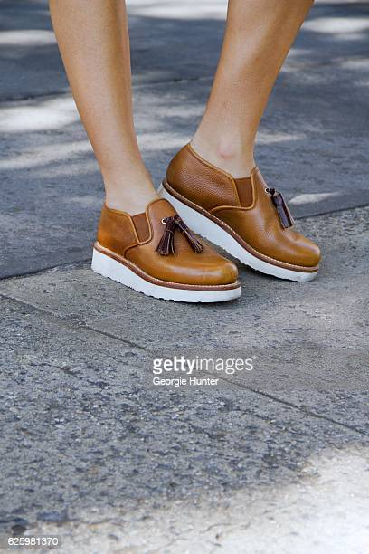 Emma Sousa wearing rounded toe tan leather slip on moccasin creepers with white wedge platform heel and tassels by Grenson on November 26 2016 in New...