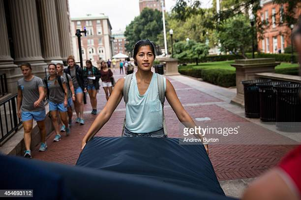 Emma Sulkowicz a senior visual arts student at Columbia University carries a mattress with the help of two strangers who met her moments before in...