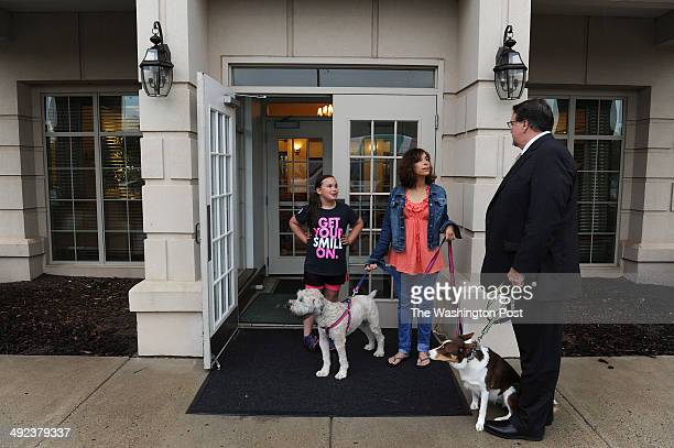Emma Sullivan left center stands next to her mother Madeline Sullivan center as she holds the leash to her dog Keeva while talking to Thomas Cooney...