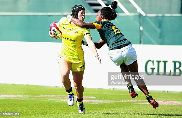 Emma Tonegate of Australia is high tackled by Veroeshka Grain of South Africa during the IRB Women's Sevens Rugby World Series at the Emirates Dubai...