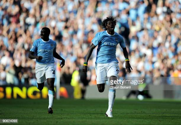 Emmanuel Adebayor of Manchester City runs towards the Arsenal fans as he celebrates scoring with teammate Kolo Toure during the Barclays Premier...
