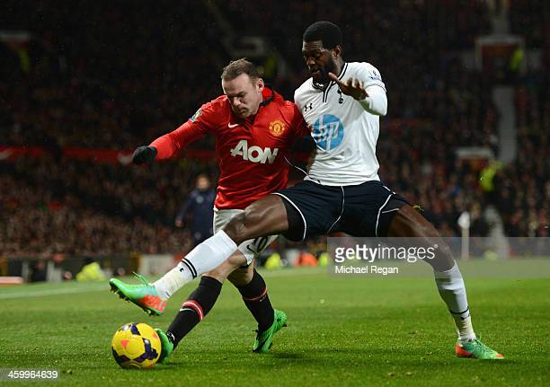 Emmanuel Adebayor of Tottenham Hotspur battles for the ball with Wayne Rooney of Manchester United during the Barclays Premier League match between...
