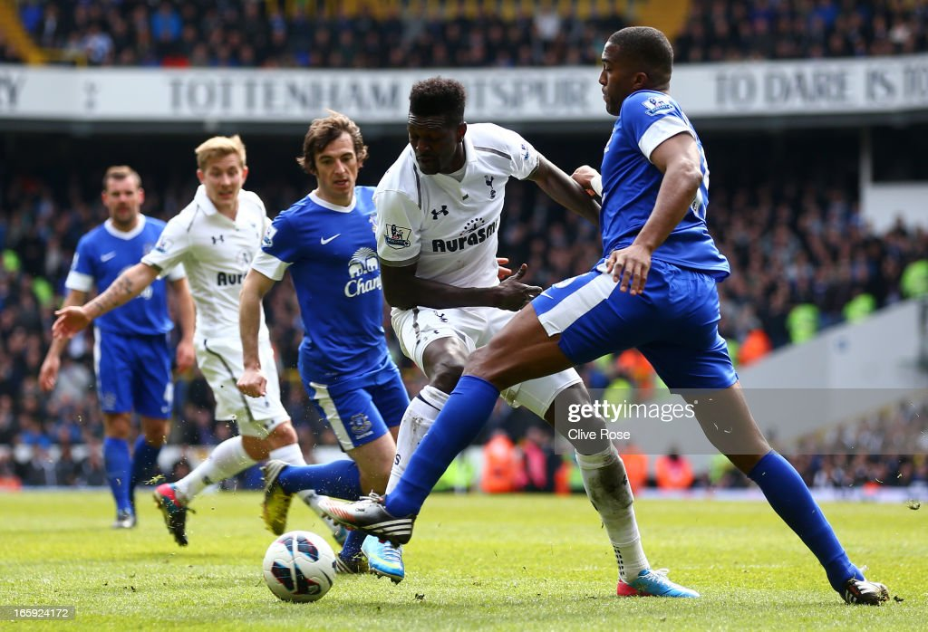 Emmanuel Adebayor of Tottenham Hotspur is marshalled by Leighton Baines and Sylvain Distin of Everton during the Barclays Premier League match between Tottenham Hotspur and Everton at White Hart Lane on April 7, 2013 in London, England.
