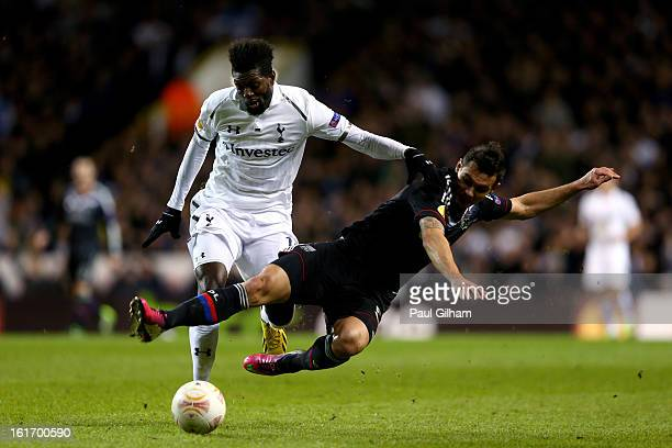 Emmanuel Adebayour of Spurs is tackled by Dejan Lovren Olympique Lyonnais during the UEFA Europa League round of 32 first leg match between Tottenham...