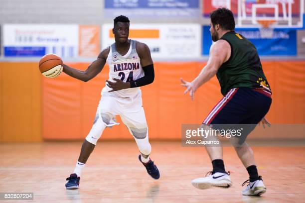 Emmanuel Akot of the Arizona Wildcats plays the ball past Francesc Pascal of the Mataro AllStars during the Arizona In Espana Foreign Tour game...