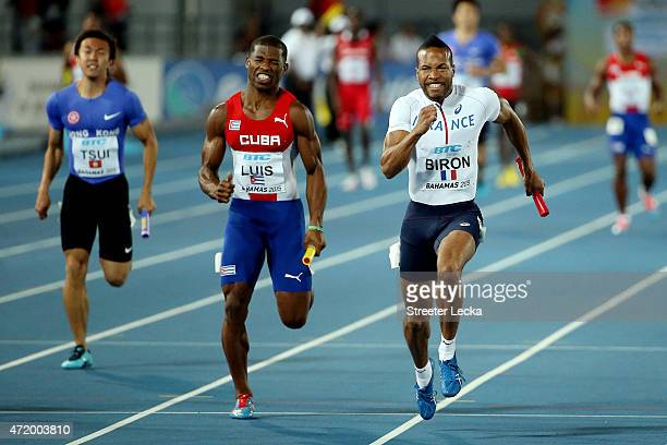 Emmanuel Biron of France leads Yadier Luis of Cuba and Chi Ho Tsui of Hong Kong China during round one of the men's 4 x 100 metres on day one of the...