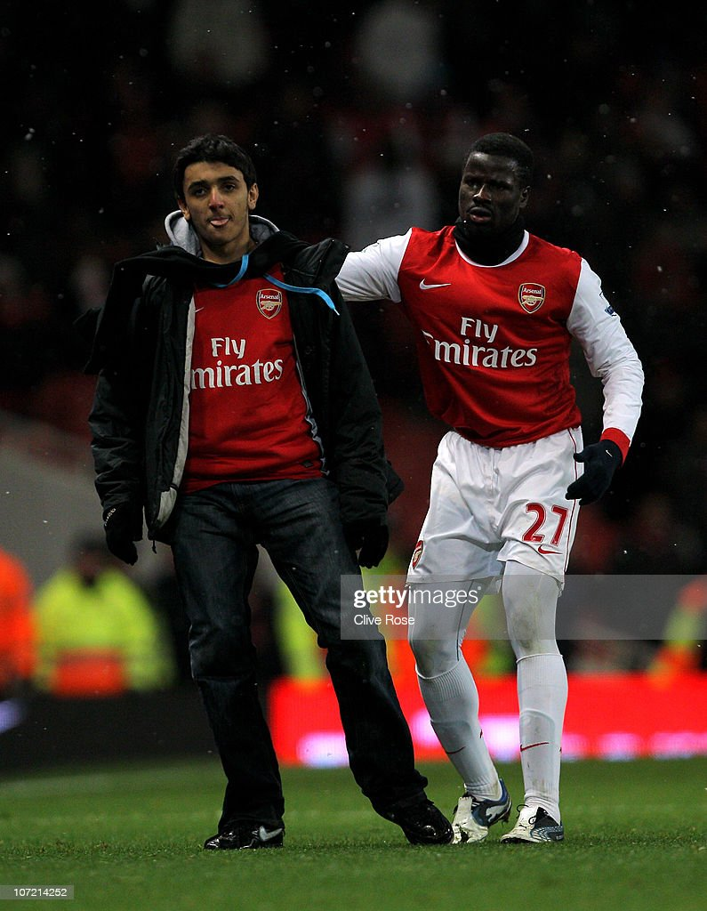 Emmanuel Eboue (R) of Arsenal apprehends a pitch invader during the Carling Cup quarter final match between Arsenal and Wigan Athletic at the Emirates Stadium on November 30, 2010 in London, England.