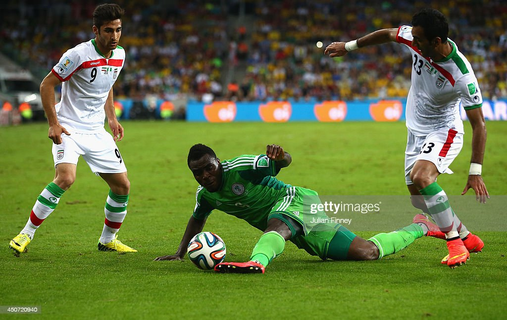 <a gi-track='captionPersonalityLinkClicked' href=/galleries/search?phrase=Emmanuel+Emenike&family=editorial&specificpeople=7487637 ng-click='$event.stopPropagation()'>Emmanuel Emenike</a> of Nigeria competes for the ball with Alireza Jahan Bakhsh (L) and <a gi-track='captionPersonalityLinkClicked' href=/galleries/search?phrase=Mehrdad+Pooladi&family=editorial&specificpeople=4074805 ng-click='$event.stopPropagation()'>Mehrdad Pooladi</a> of Iran (R) during the 2014 FIFA World Cup Brazil Group F match between Iran and Nigeria at Arena da Baixada on June 16, 2014 in Curitiba, Brazil.