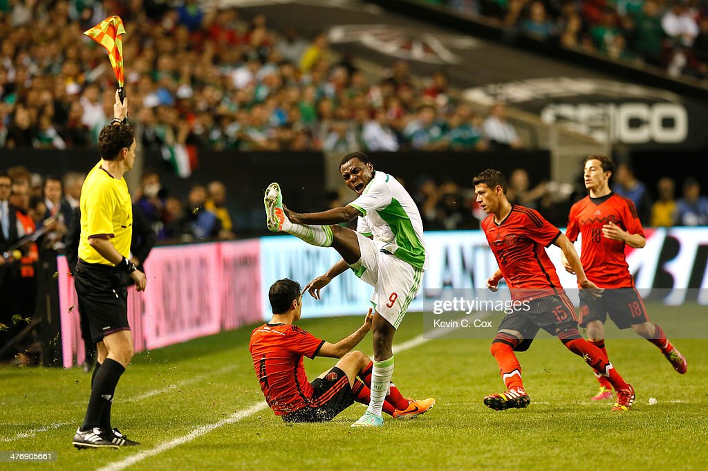 <a gi-track='captionPersonalityLinkClicked' href=/galleries/search?phrase=Emmanuel+Emenike&family=editorial&specificpeople=7487637 ng-click='$event.stopPropagation()'>Emmanuel Emenike</a> #9 of Nigeria earns a yellow card as he reacts towards Assistant Referee Peter Manikowski at Georgia Dome on March 5, 2014 in Atlanta, Georgia.