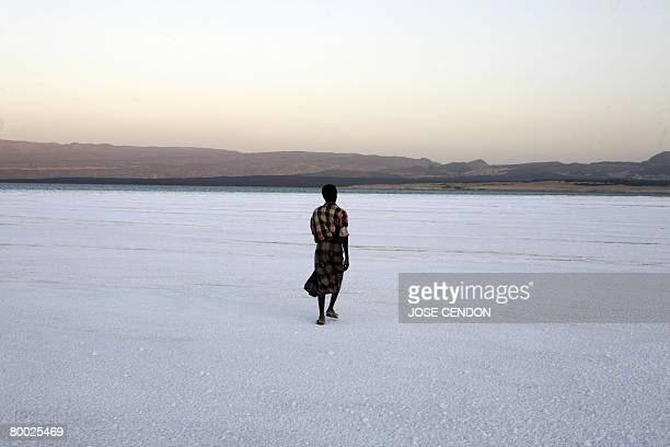 Emmanuel GOUJON A man walks on solid salt of Lake Assal on February 10 2008 in Djibouti The development of tourism in Djibouti is one of the...