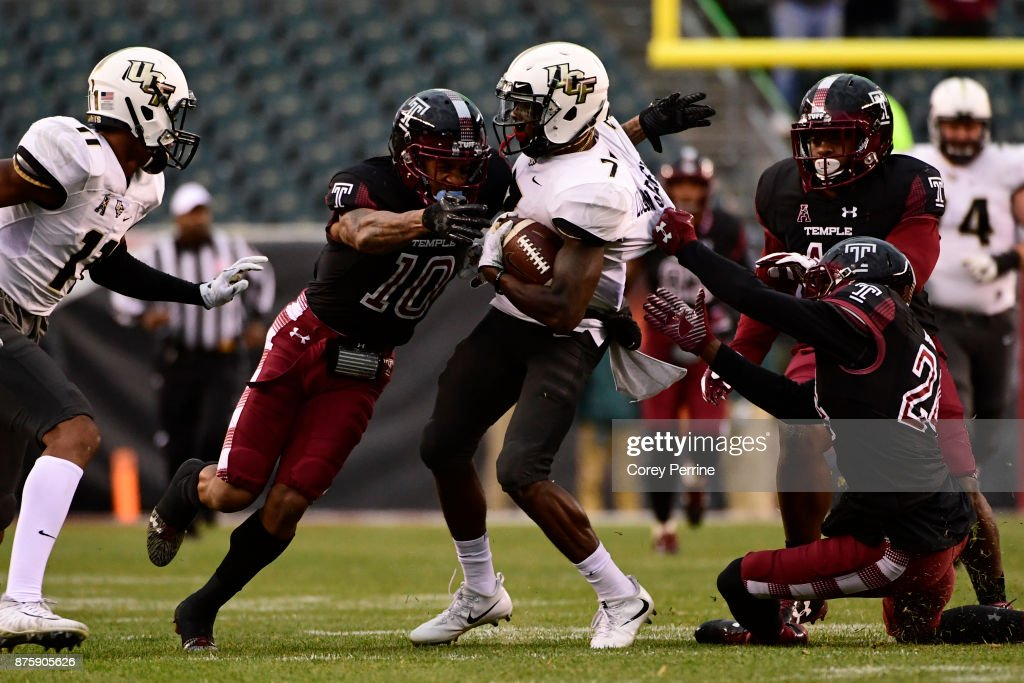 Emmanuel Logan-Greene #7 of the UCF Knights is pulled down by Mike Jones #10 (L) of the Temple Owls and teammate Kimere Brown #24 at Lincoln Financial Field on November 18, 2017 in Philadelphia, Pennsylvania. UCF defeated Temple 45-19.